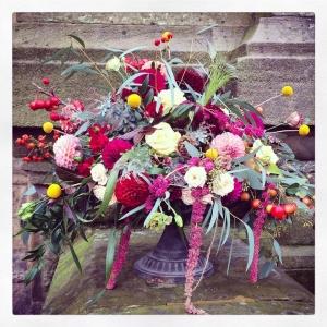 Autumn urn arrangement of dahlias, craspedia, amaryanthus, chrysanthmum blooms, crab apples, hips